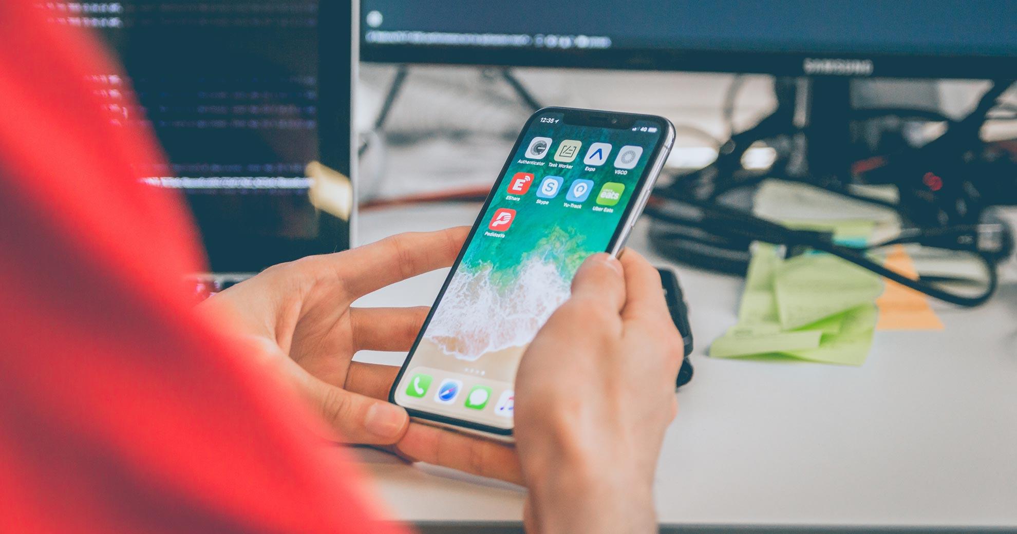 uma pessoa está segunrando o celular nas mãos