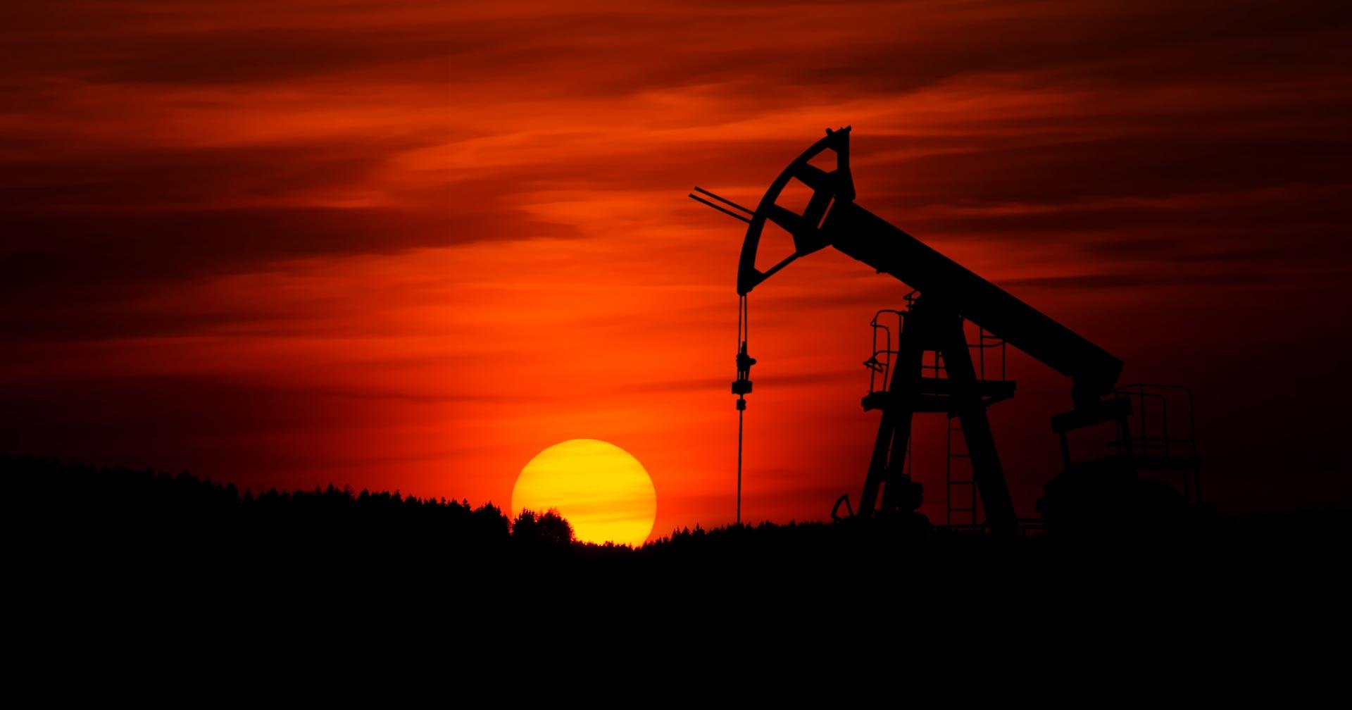 paisagem do por-do-sol e ao fundo uma silheta de bomba de óleo
