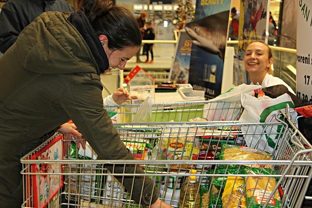 Menina com carrinho de compras no supermercado